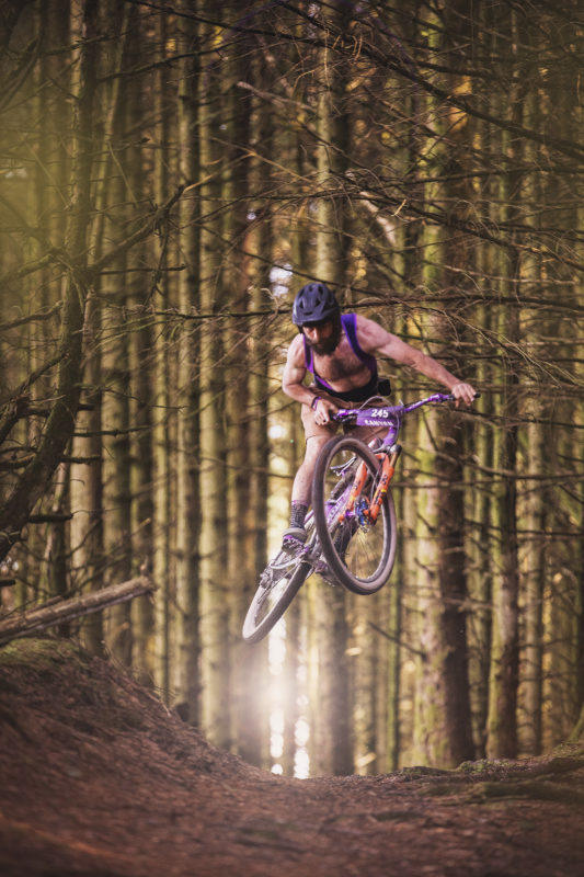 Grinduro, mountain bike rider jumping in the woods