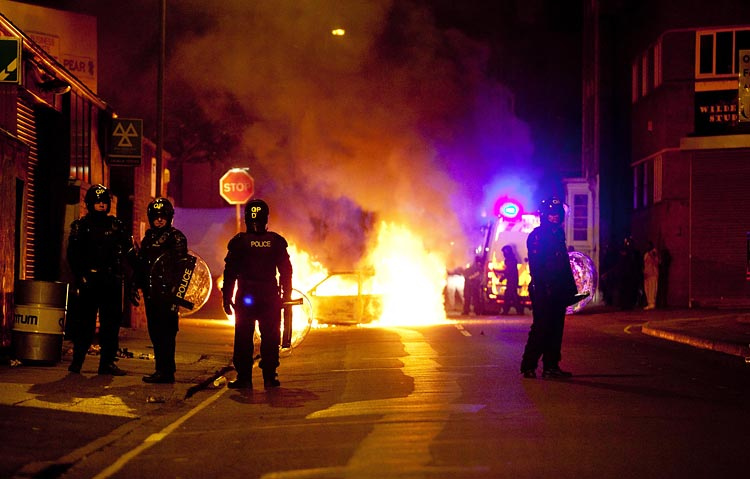 Riot police stand by a burning car in Bristol / Adam Gasson / adamgasson.com