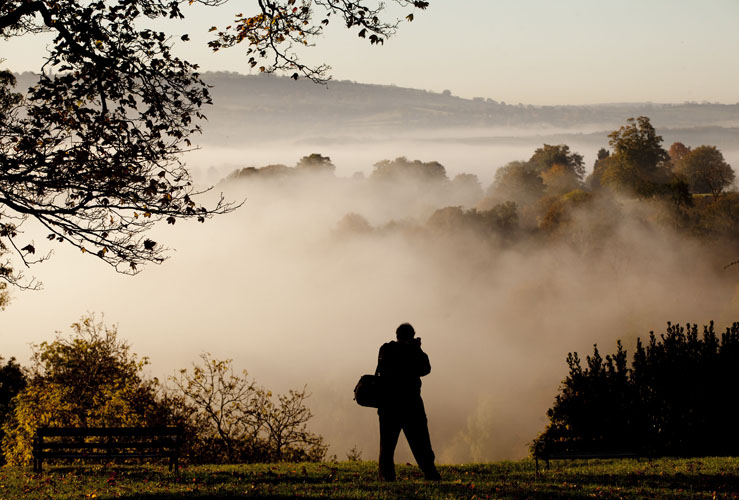 A man stops to take a picture as Bristol wakes up to heavy fog by Adam Gasson