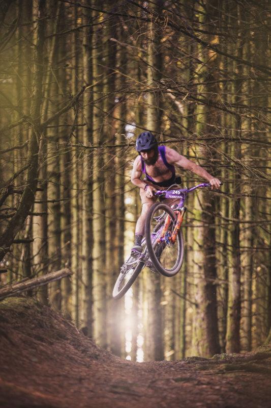 Grinduro, mountain bike rider jumping in the woods