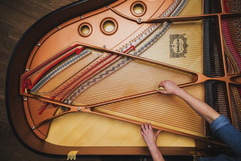 Yamaha piano technician working on an open piano